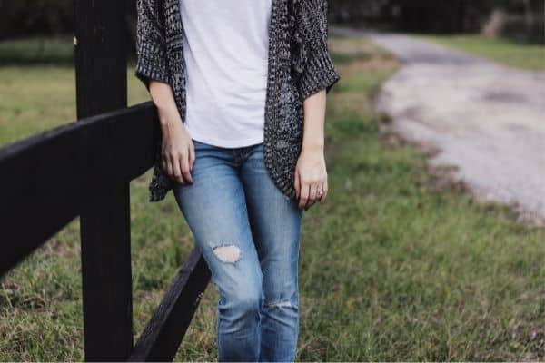 women leaning against a fence with a sweater, white t-shirt, and distressed jeans on.