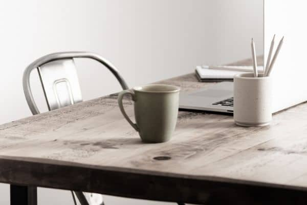 home office with farm house style table for a desk, with a cup of coffee and laptop