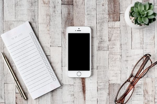 note pad, phone, and glasses laying on a wood slab