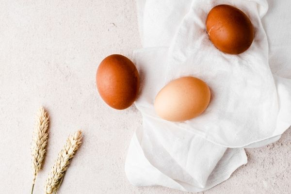eggs sitting on a soft cloth with wheat.
