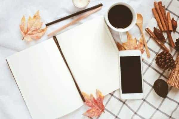 planner on a table with phone, coffee and fall leaves.