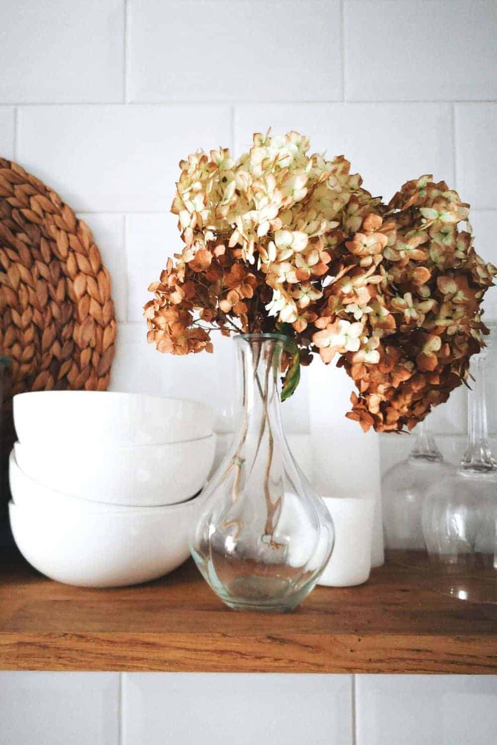 neutral fall flowers in a vase and bowls for decor