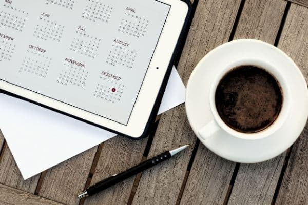 iPad and cup of coffee sitting on a table.