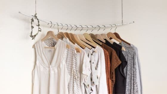 minimalist wardrobe clothes having on a bar.